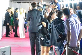 In the far left: Kate in a white dress about to make her way inside